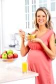 12137517-lachende-mooie-zwangere-vrouw-het-eten-van-granen-in-de-keuken